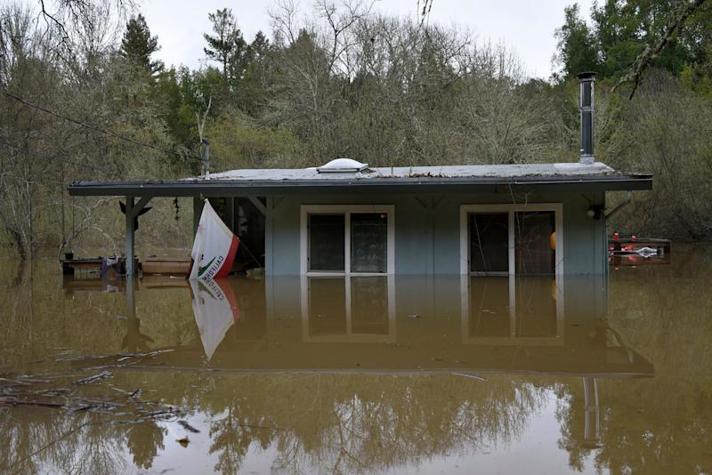 A California state flag hangs from the front of a home submerged in the flood waters of the Russian River in Forestville, Calif., on Feb. 27, 2019. (Photo: Michael Short/AP)