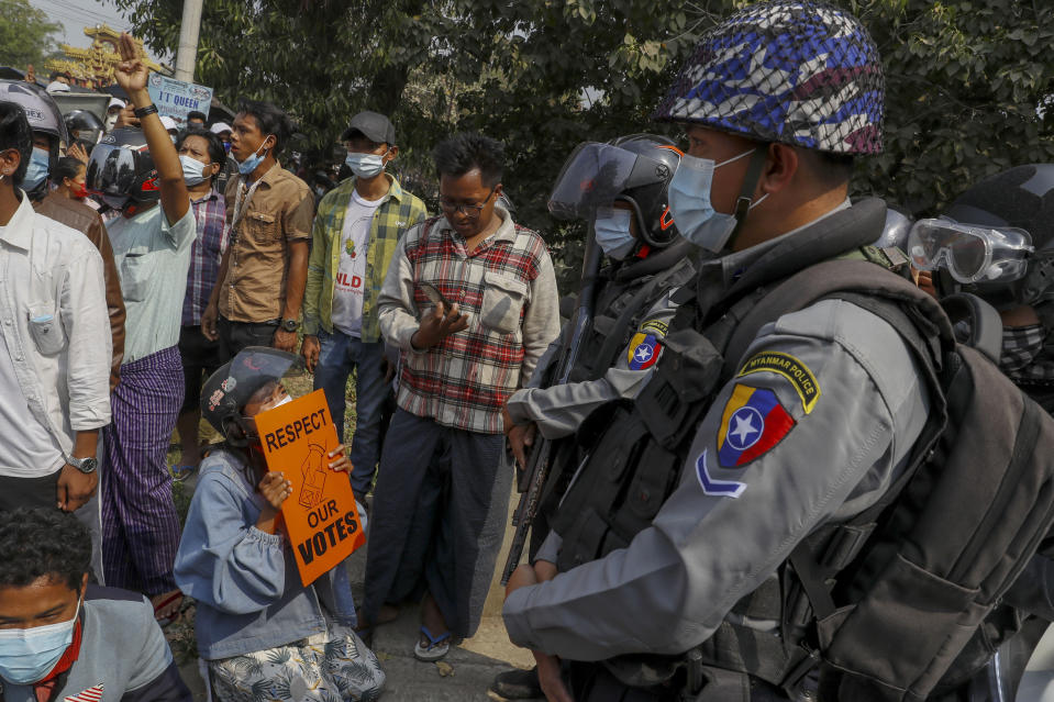 Police stand guard as demonstrators protest against the military junta's arrest and chagrining of National League for Democracy party lawmakers, Mandalay region Chief Minister Zaw Myint Maung and Mayor Ye Lwin, outside Aung Myay Thar Zan Township court in Mandalay, Myanmar, Thursday, Feb. 18, 2021. Tens of thousands of demonstrators flooded the streets of Myanmar's biggest city, Yangon, Wednesday, in one of largest protests yet of a coup, despite warnings from a U.N. human rights expert that recent troop movements could indicate the military was planning a violent crackdown. (AP Photo)