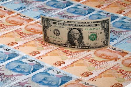 FILE PHOTO: A U.S. dollar banknote is seen on top of 50 and 100 Turkish lira banknotes in this picture illustration in Istanbul