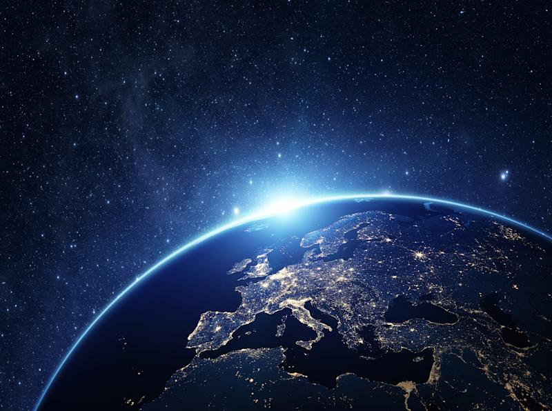 Earth viewed from space at night. The European continent is in view, lit up by city lights.