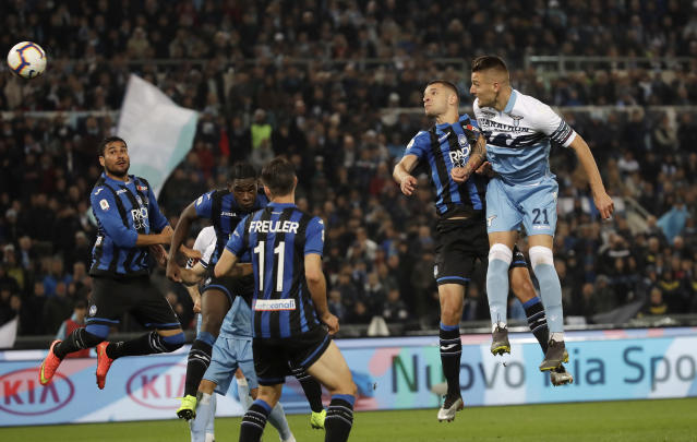 Lazio's Sergej Milinkovic Savic, right, scores his side's opening goal during the Italian Cup soccer final match between Lazio and Atalanta, at the Rome Olympic stadium, Wednesday, May 15, 2019. (AP Photo/Alessandra Tarantino)