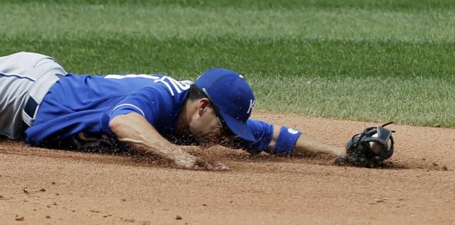 Kansas City Royals' Jamey Carroll slides in the dirt after catching a ball hit by Cleveland Indians' Jason Kubel in the fourth inning of a baseball game, Wednesday, Sept. 11, 2013, in Cleveland. Kubel was out. (AP Photo/Tony Dejak)