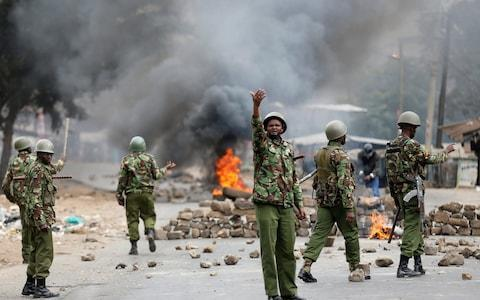 <span>Anti riot policemen deploy after protesters set tyres on fire in Mathare, Nairobi</span> <span>Credit: REUTERS </span>