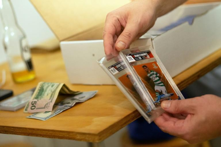 Sports card collectors strike a deal on soccer cards at Bleecker Trading in New York on July 06, 2021