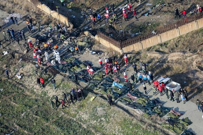 Rescue teams are pictured among bodies and debris at the crash site (AFP Photo/Rouhollah VAHDATI)