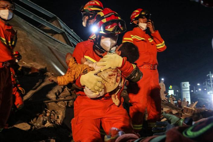 "A boy is rescued from the rubble of a collapsed hotel in Quanzhou, in eastern China's Fujian province, early on March 8, 2020. <span class=""copyright"">(AFP/Getty Images)</span>"