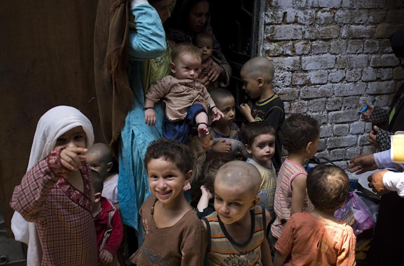 In this Tuesday, Aug. 27, 2013, photo, Pakistani children of four families living in a house wait to be immunized against polio in Rawalpindi, Pakistan. Pakistan's health authorities confirmed five new polio cases from tribal areas where Islamic militants banned the vaccine over a year ago and many more suspected cases, one of a series of outbreaks this year in parts of the country where security threats have kept out vaccination teams. (AP Photo/B.K. Bangash)