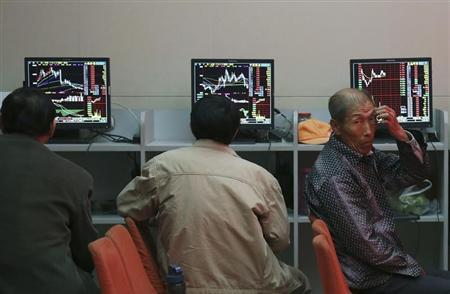 Investors sit in front of computer screens at a brokerage house in Shenyang, Liaoning province, May 12, 2014. China's main stock index closed at its best level in two-and-a-half weeks on Monday, underpinned by Beijing's pledge to push ahead with a broad range of capital market reforms and a surging commodities sector. REUTERS/Stringer