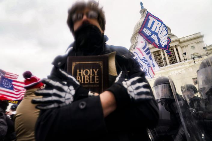 In this Wednesday, Jan. 6, 2021 file photo, a man holds a Bible as President Donald Trump's supporters gather outside the Capitol in Washington.