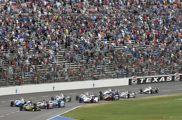 FILE - In this June 10, 2017, file photo, pole-sitter Charlie Kimball, front left, leads the field at the start of an IndyCar auto race at Texas Motor Speedway in Fort Worth, Texas. IndyCar has gotten the green flag to finally start its season in Texas. The race will be run June 6 without spectators at Texas Motor Speedway. (AP Photo/Larry Papke, File)