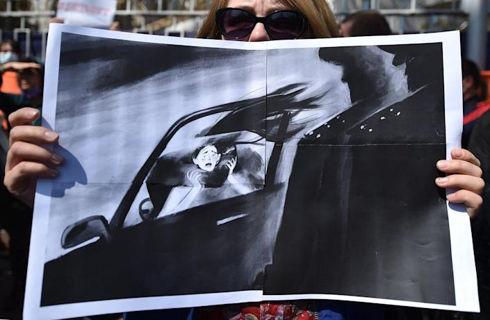 Woman holds a drawing depicting a scared woman being taken away in a car