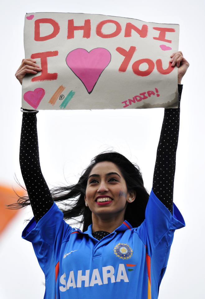 """An Indian cricket fan holds a banner reading """"Dhoni I [love] you"""" referring to Indian captain Mahendra Dhoni during the 2013 ICC Champions Trophy cricket match between Pakistan and India at Edgbaston in Birmingham, England on June 15, 2013. AFP PHOTO/GLYN KIRK"""