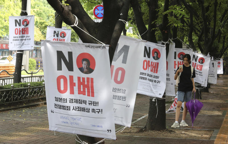 "A South Korean woman takes pictures of banners with image of Japanese Prime Minister Shinzo Abe to denounce Japan's trade restrictions on South Korea on a street in Seoul, South Korea, Monday, Aug 12, 2019. South Korea said Monday that it has decided to remove Japan from a list of nations receiving preferential treatment in trade in what was seen as a countermeasure to Tokyo's recent decision to downgrade Seoul's trade status amid a diplomatic row. The sign reads ""No Abe."" (AP Photo/Ahn Young-joon)"