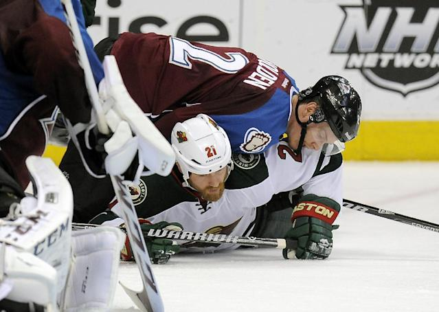 Colorado Avalanche defenseman Nick Holden, top, fights for the puck with Minnesota Wild center Kyle Brodziak, bottom, in the second period in Game 5 of an NHL hockey first-round playoff series on Saturday, April 26, 2014, in Denver. The Avalanche won 4-3 in overtime. (AP Photo/Chris Schneider)
