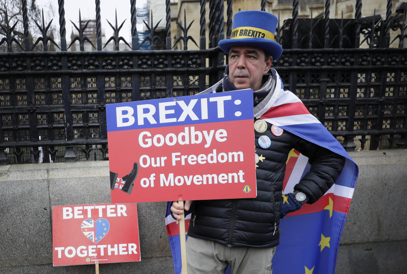 Anti-Brexit campaigner Steve Bray holds banners as he stands outside Parliament in London, Thursday, Jan. 30, 2020. Although Britain formally leaves the European Union on Jan. 31, little will change until the end of the year. Britain will still adhere to the four freedoms of the tariff-free single market – free movement of goods, services, capital and people. (AP Photo/Kirsty Wigglesworth)