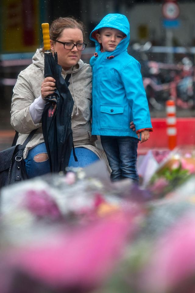 <p>A woman and child view flowers shortly after a minutes silence near the scene of Saturday's terrorist attack, on June 6, 2017 in London, England. (Photo: Carl Court/Getty Images) </p>
