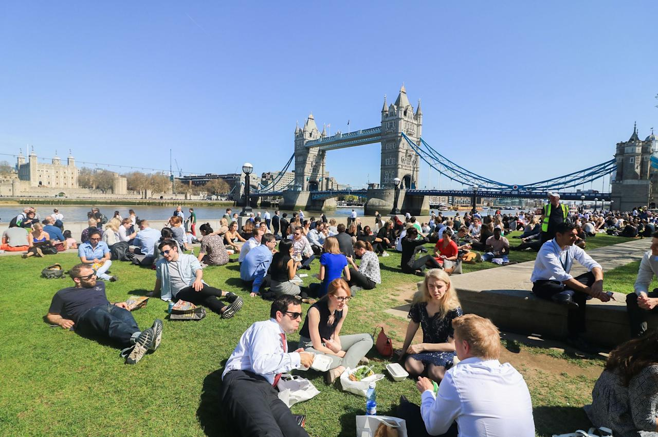 <p>Lunch workers enjoy the spring sunshine in their lunch hour on London Riverside. (Rex) </p>