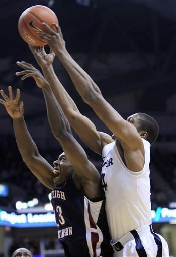 Xavier forward Travis Taylor, right, reaches over Fairleigh Dickinson guard Lonnie Robinson (23) for a rebound during the first half of an NCAA college basketball game, Friday, Nov. 9, 2012, in Cincinnati. (AP Photo/Al Behrman)