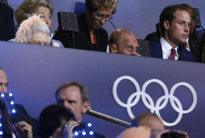 Britain's Queen Elizabeth II, top left, Britain's Prince Philip, the Duke of Edinburgh, center, and Britain's Prince William, the Duke of Cambridge, right, watch the Opening Ceremony at the 2012 Summer Olympics, Friday, July 27, 2012, in London. (AP Photo/Matt Dunham)