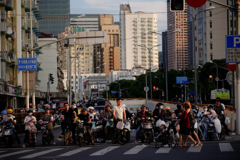 People riding bicycles and motorbikes wait in traffic, amid the coronavirus disease pandemic, in Shanghai