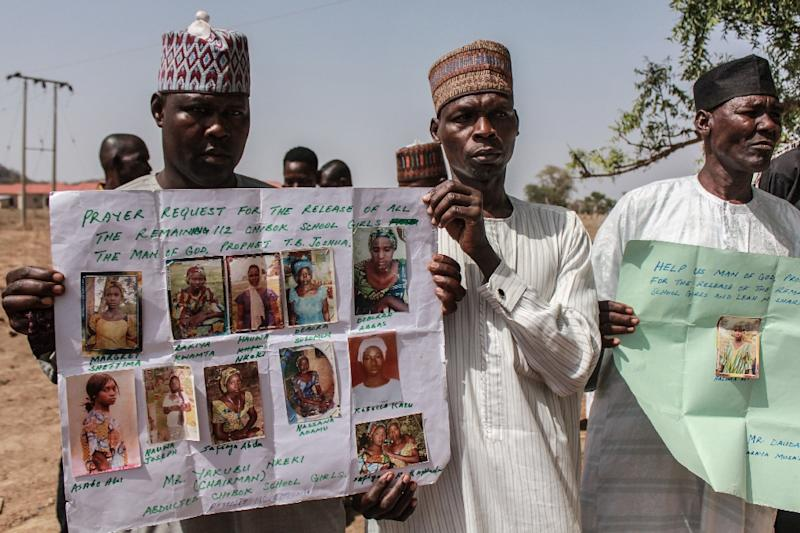 Parents and relatives hold portraits of their girls during a commemoration five years after they were abducted by Boko Haram Jihadists who stormed the Chibok girls' boarding school (AFP Photo/Audu Ali MARTE)