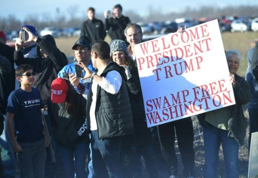Trump supporters hold a sign greeting the US president to the rally in Washington, Michigan