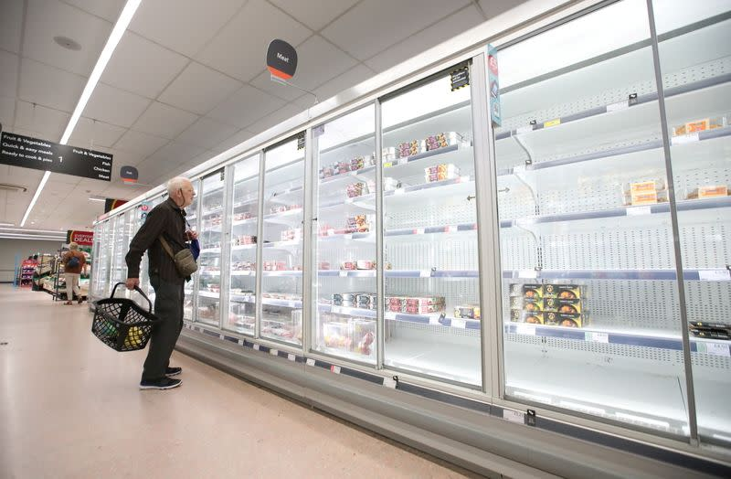 A shopper looks at produce and empty shelves of the meat aisle in Co-Op supermarket, Harpenden
