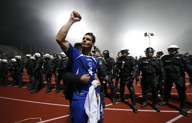Bosnia's Emir Spahic celebrates victory during the World Cup group G qualifying soccer match between Lithuania and Bosnia in Kaunas, Lithuania, Tuesday, Oct. 15, 2013. (AP Photo/Mindaugas Kulbis)