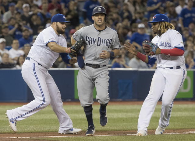 San Diego Padres' Ian Kinsler gets caught in a rundown between third and home plate by Toronto Blue Jays' Rowdy Tellez, left, with the tag and third baseman Vladmir Guerrero Jr. during the seventh inning of a baseball game Friday, May 24, 2019, in Toronto. (Fred Thornhill/The Canadian Press via AP)