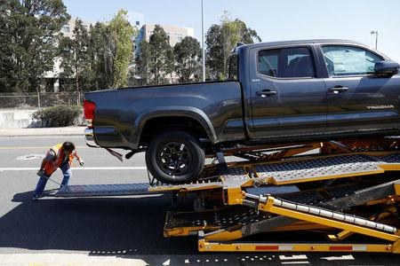 A worker moves a ramp on a car carrier trailer outside City Toyota in Daly City, California