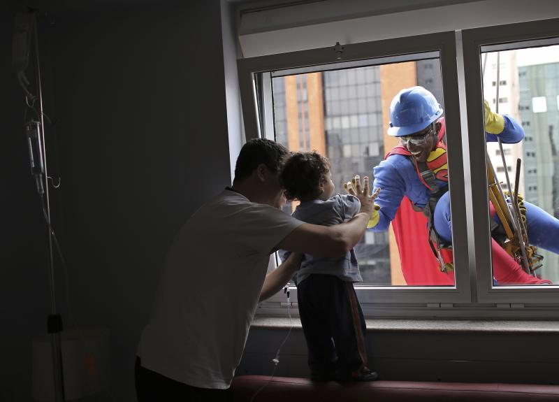 Men dressed as cartoon characters meet with children's hospital patients in Sao Paulo