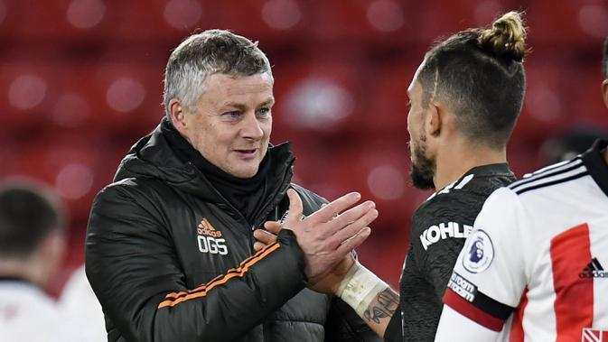 Manajer Manchester United, Ole Gunnar Solskjaer (kiri), memberi selamat pemainnya, bek Alex Telles, usai laga lanjutan Liga Inggris 2020/21 pekan ke-13 melawan Sheffield United di Bramall Lane, Sheffield, Kamis (17/12/2020). Manchester United menang 3-2 atas Sheffield United. (AFP/Peter Powell/Pool)