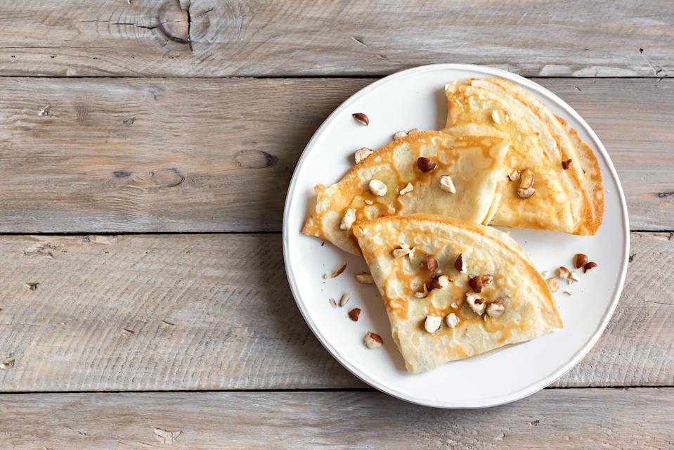 Crepes Suzette with honey and nuts on white plate over wooden background, copy space. Delicious homemade Crepes for breakfast.