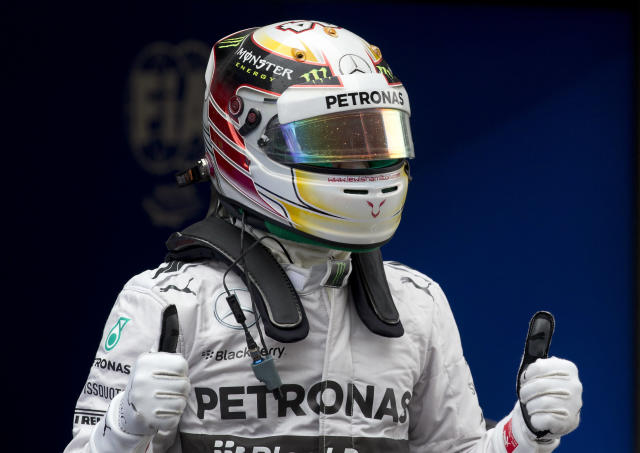 Mercedes driver Lewis Hamilton of Britain celebrates after he won the pole position for Sunday's Chinese Formula One Grand Prix at Shanghai International Circuit in Shanghai, China Saturday, April 19, 2014. (AP Photo/Andy Wong)