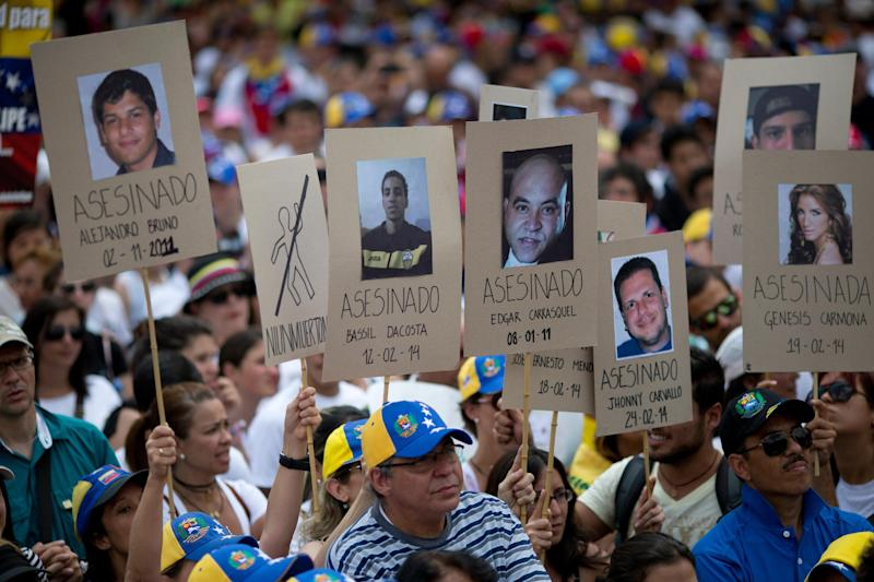 Demonstrators hold up posters with images of Venezuelans who were killed in the past two weeks during the recent unrest, at a rally with human rights activists in Caracas, Venezuela, Friday, Feb. 28, 2014. The start of a weeklong string of holidays leading up to the March 5 anniversary of former President Hugo Chavez's death has not completely pulled demonstrators from the streets as the government apparently hoped. President Nicolas Maduro announced this week that he was adding Thursday and Friday to the already scheduled long Carnival weekend that includes Monday and Tuesday off, and many people interpreted it as an attempt to calm tensions. (AP Photo/Rodrigo Abd)