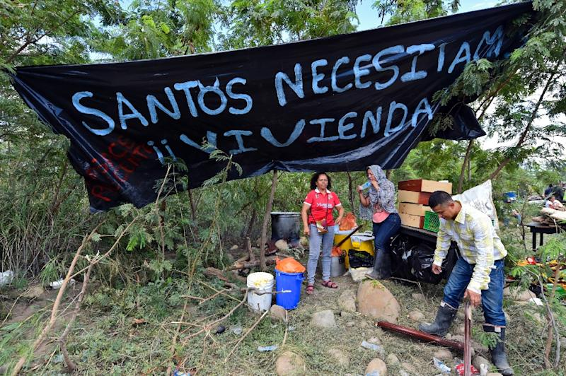 """A Colombian family is seen next to a banner reading """"Santos, we need housing"""" (referring to Colombian President Juan Manuel Santos) in Cucuta, Colombia after crossing the border from Venezuela on August 26, 2015 (AFP Photo/Luis Acosta)"""