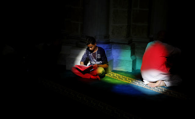 <p>A Palestinian man reads verses of the Quran, Islam's holy book, during the month of Ramadan at al-Omari mosque in Gaza City, Monday, May 29, 2017. (AP Photo/Hatem Moussa) </p>
