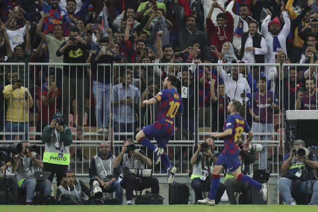 Barcelona's Lionel Messi, left, celebrates after scoring his side's opening goal during the Spanish Super Cup semifinal soccer match between Barcelona and Atletico Madrid at King Abdullah stadium in Jiddah, Saudi Arabia, Thursday, Jan. 9, 2020. (AP Photo/Hassan Ammar)