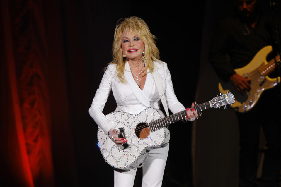 """FILE - Dolly Parton performs in concert on July 31, 2015, in Nashville, Tenn. Parton is asking Tennessee lawmakers to withdraw a bill that would erect a statue of her on the Capitol grounds in Nashville. In a statement released Thursday, Parton says that given current events, she doesn't think being put on a pedestal """"is appropriate at this time."""" (Photo by Wade Payne/Invision/AP, File)"""