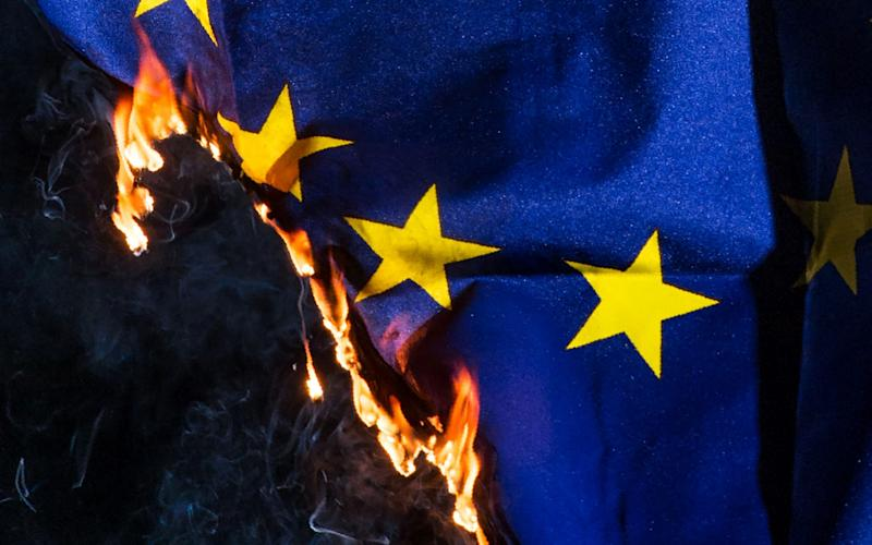 A European Union flag as it burns - Credit: OLI SCARFF/AFP