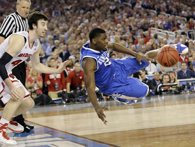 Kentucky forward Alex Poythress (22) saves the ball from going out as Wisconsin forward Frank Kaminsky (44) defends during the second half of the NCAA Final Four tournament college basketball semifinal game Saturday, April 5, 2014, in Arlington, Texas. (AP Photo/Eric Gay)