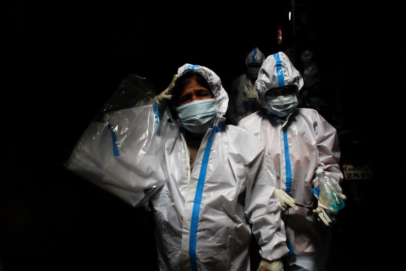 A health worker in personal protective equipment reacts as she and the rest of the team walk through an alley during a check up campaign for the coronavirus disease (COVID-19) at a slum area in Mumbai