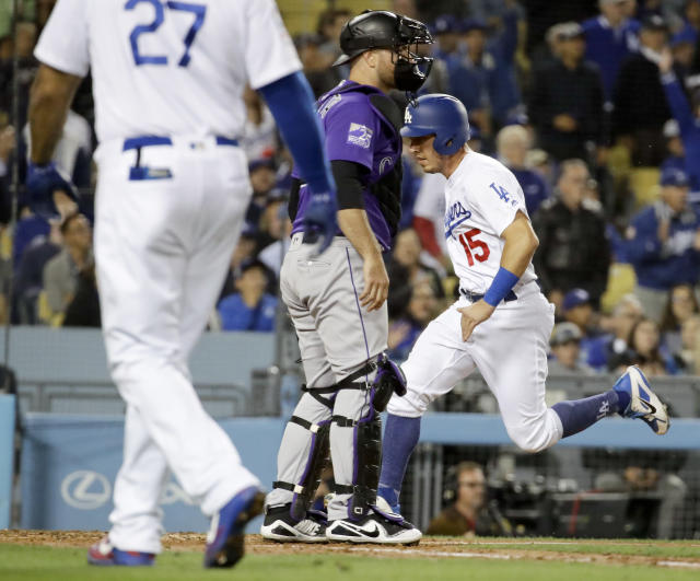 Los Angeles Dodgers' Austin Barnes, right, scores past Colorado Rockies catcher Chris Iannetta on a sacrifice fly by Matt Kemp during the fifth inning of a baseball game in Los Angeles, Wednesday, May 23, 2018. (AP Photo/Chris Carlson)