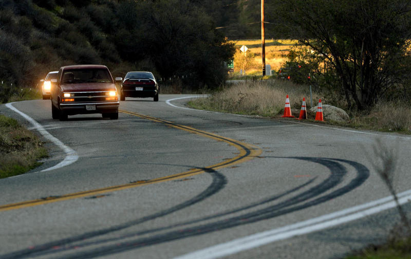 Skid marks from the weekend's fatal bus cash remain on the pavement as morning commuters drive along Highway 38 for the first time since the road was reopened, Tuesday, Feb. 5, 2013 in Yucaipa, Calif. The crash involved two other vehicles and left seven people dead and more than 30 people injured. The tour bus originated from Tijuana and was driving down from Big Bear Lake. (AP Photo/The Sun, Gabriel Luis Acosta) VENTURA COUNTY STAR OUT; RIVERSIDE PRESS-ENTERPRISE OUT; THE VICTOR VALLEY DAILY PRESS OUT