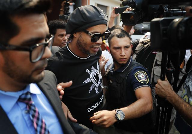 Former Brazilian soccer star Ronaldinho, whose full name is Ronaldo de Assis Moreira, center, leaves the attorney general's office in Asuncion, Paraguay, Thursday, March 5, 2020. Ronaldinho and his brother were detained by Paraguayan police for allegedly entering the country with falsified passports on Wednesday. (AP Photo/Jorge Saenz)