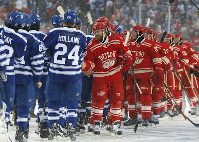 Detroit Red Wings left wing Henrik Zetterberg leads his team as they shake the hands of the Toronto Maple Leafs after the Winter Classic outdoor NHL hockey game at Michigan Stadium in Ann Arbor, Mich., Wednesday, Jan. 1, 2014. The Maple Leafs won 3-2. (AP Photo/Paul Sancya)