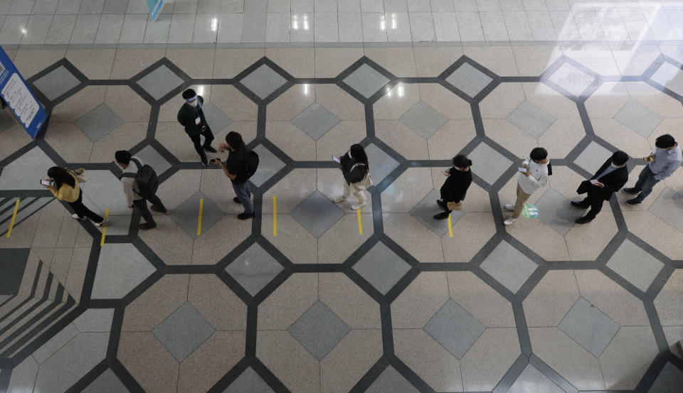 Visitors wearing face masks as a precaution against the coronavirus, wait in a line while maintaining social distancing outside of an exhibition hall in Seoul, South Korea, Wednesday, Oct. 21, 2020. (AP Photo/Lee Jin-man)