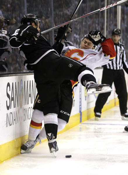 Los Angeles Kings defenseman Jake Muzzin, left, checks Calgary Flames left wing Jiri Hudler during the first period of an NHL hockey game in Los Angeles, Monday, Oct. 21, 2013. (AP Photo/Chris Carlson)