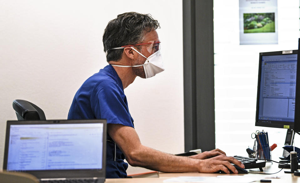 A doctor with a face mask to protect from coronavirus works in his office on a computer during a presentation for media of new emergency rooms at the University Hospital in Essen, Germany, Thursday, March 26, 2020. Hospitals in Germany ready themselves for an expected growing number of COVID-19 patients in the coming weeks. The new coronavirus causes mild or moderate symptoms for most people, but for some, especially older adults and people with existing health problems, it can cause more severe illness or death. (AP Photo/Martin Meissner)