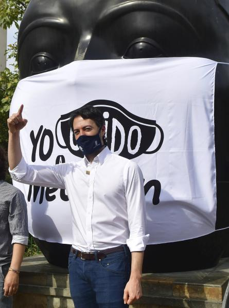 In this June 8, 2020 photo, Mayor Daniel Quintero, wearing a protective face mask as a measure to curb the spread of the new coronavirus, talks to the media during a COVID-19 prevention campaign, in Medellin, Colombia. Quintero, Medellin's youngest mayor ever, is an engineer by training who began holding COVID-19 prep meetings in January, weeks after taking office. The virus was a blip on the radar for most Latin American governments back then. (AP Photo/Luis Benavides)